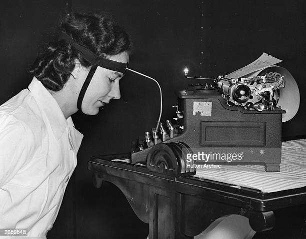 A disabled woman typing with the help of a device attached to her head at an exhibition of aids for the Disabled in London