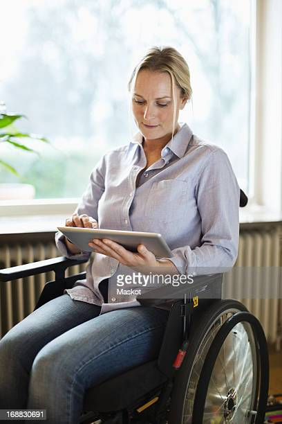 disabled woman using digital tablet while sitting in wheelchair at home - westeuropa stock-fotos und bilder