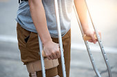 Disabled woman with crutches or walking stick or knee support standing in back side,half body.