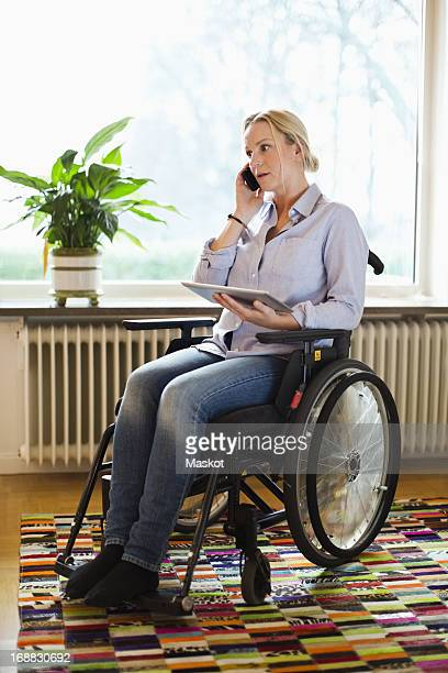 disabled woman with digital tablet using mobile phone while sitting in wheelchair at home - westeuropa stock-fotos und bilder