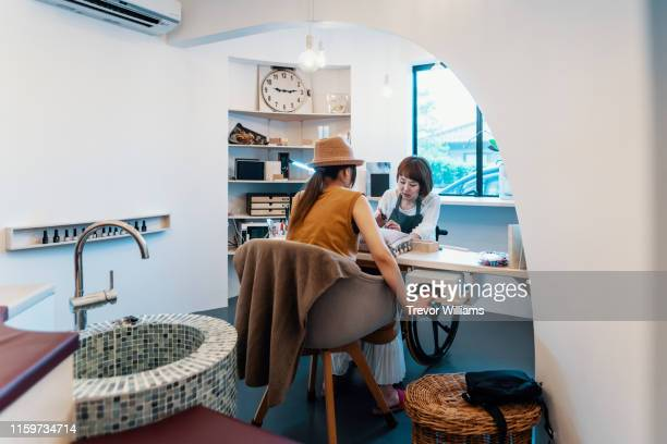 disabled woman working in a her own beauty salon - differing abilities female business fotografías e imágenes de stock