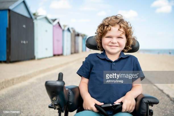 disabled young boy sitting in wheelchair by beach huts - physical disability stock pictures, royalty-free photos & images