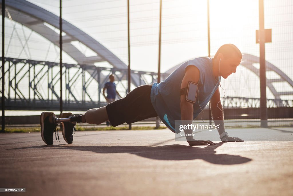 Disabled young man working on arms on outdoors court ,push ups exercise : Stock Photo