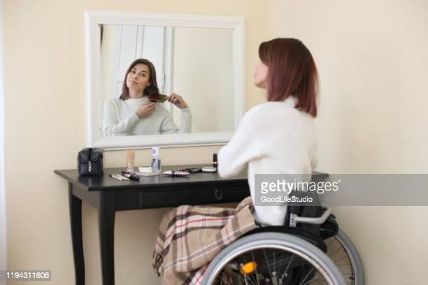disabled young woman combing her hair - penteando imagens e fotografias de stock