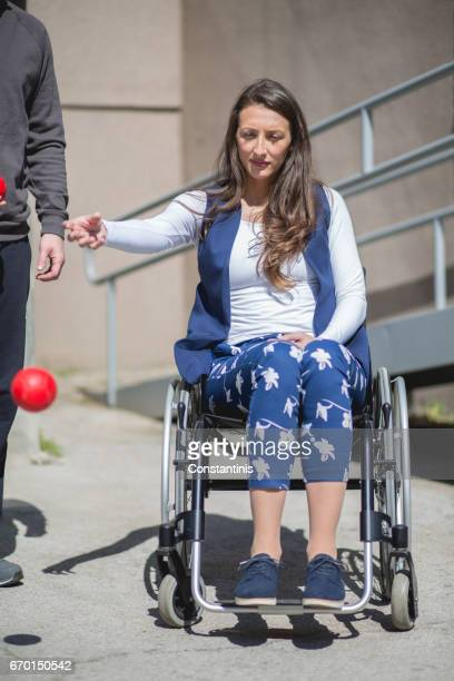disabled young woman on wheelchair playing boccia on asphalt court. - paraplegic stock photos and pictures