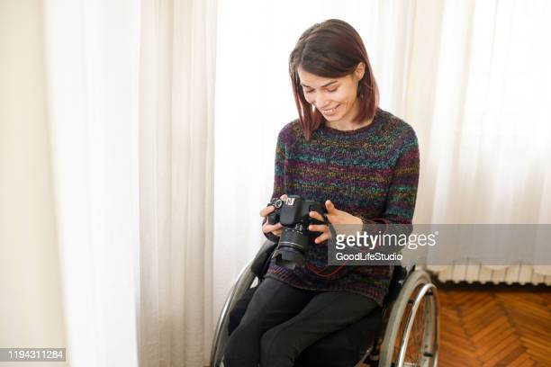 disabled young woman photographing - photographer stock pictures, royalty-free photos & images
