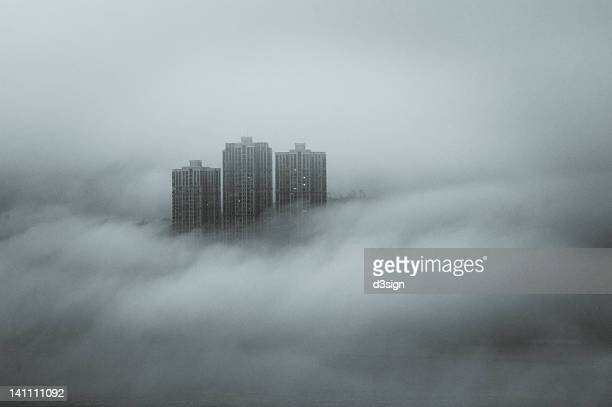 Disappearing skyscraper by fog and cloud