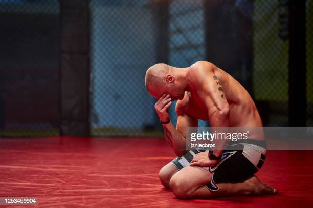 disappointed athlete after lost fight - combat sport stock pictures, royalty-free photos & images