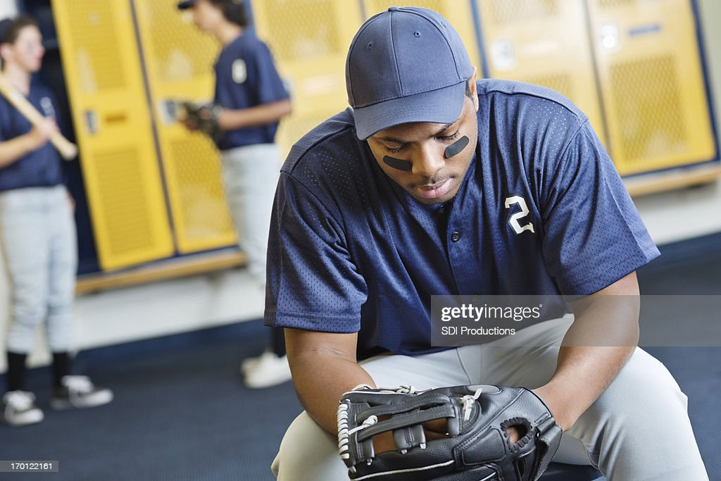 Disappointed Baseball Player In High School Locker Room Stock Photo