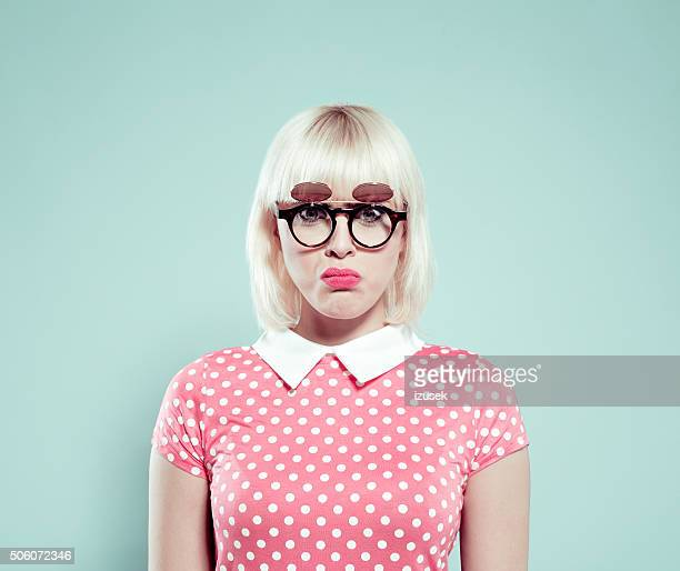 disappointed blonde young woman wearing polka dotted dress and sunglasses - fringe dress stock pictures, royalty-free photos & images