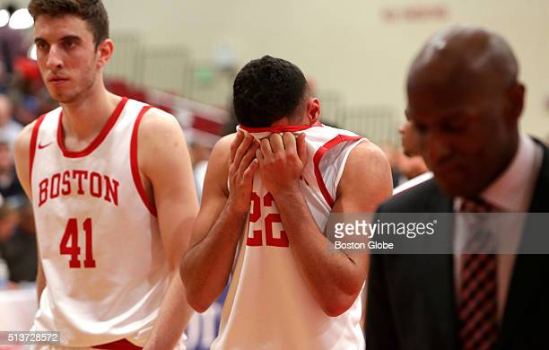 A disappointed Boston University Terriers forward Dylan Haines right forward Nathan Dieudonne center and head coach Joe Jones head off the court...