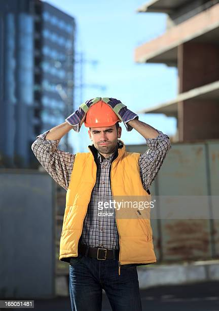 Disappointed builder or worker is thinking about problems.