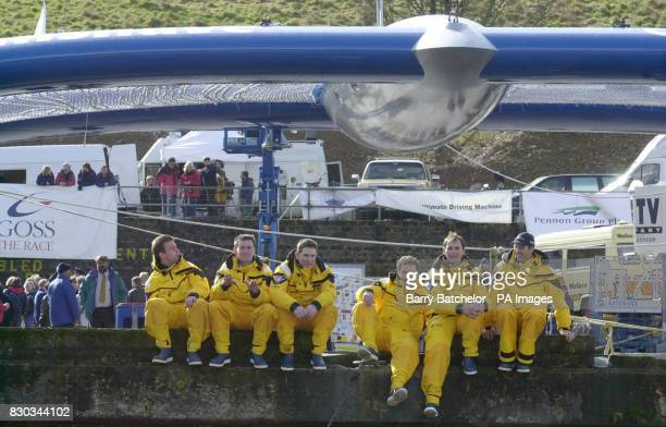 Disappointed crew sit alongside the water at Totnes in front of the Team Philips catamaran after the scheduled launch was called off because of high...