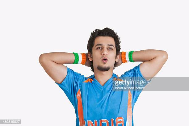Disappointed cricket fan with hands behind head looking away over white background