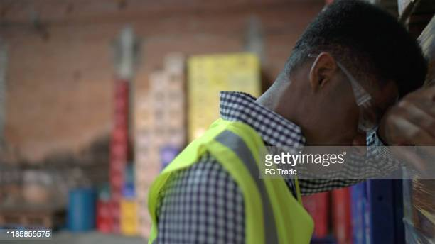 disappointed employee at warehouse - head in hands stock pictures, royalty-free photos & images