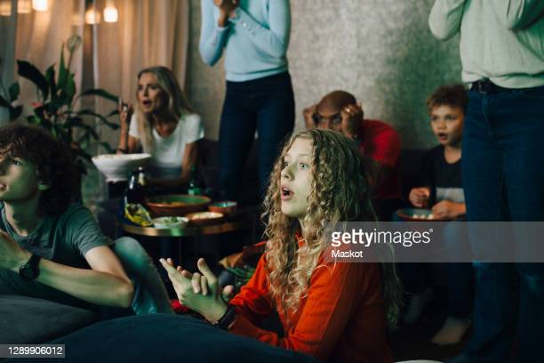 disappointed family watching sports on tv at night - television stock pictures, royalty-free photos & images