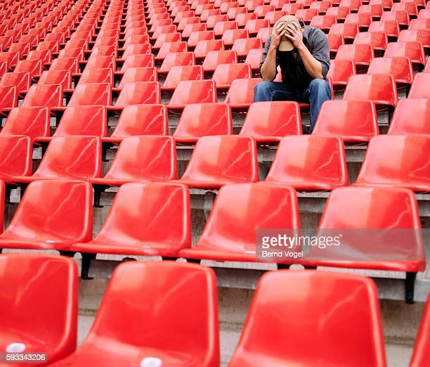 disappointed fan lingering at a stadium - defeat stock pictures, royalty-free photos & images