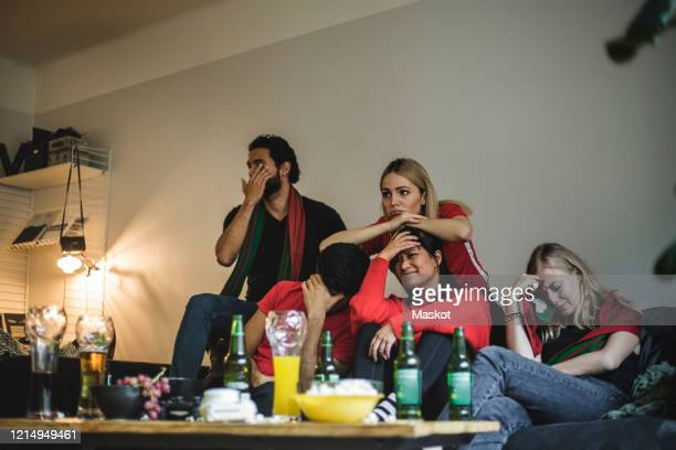 disappointed fans watching soccer match while sitting on sofa at home - friendly match stockfoto's en -beelden