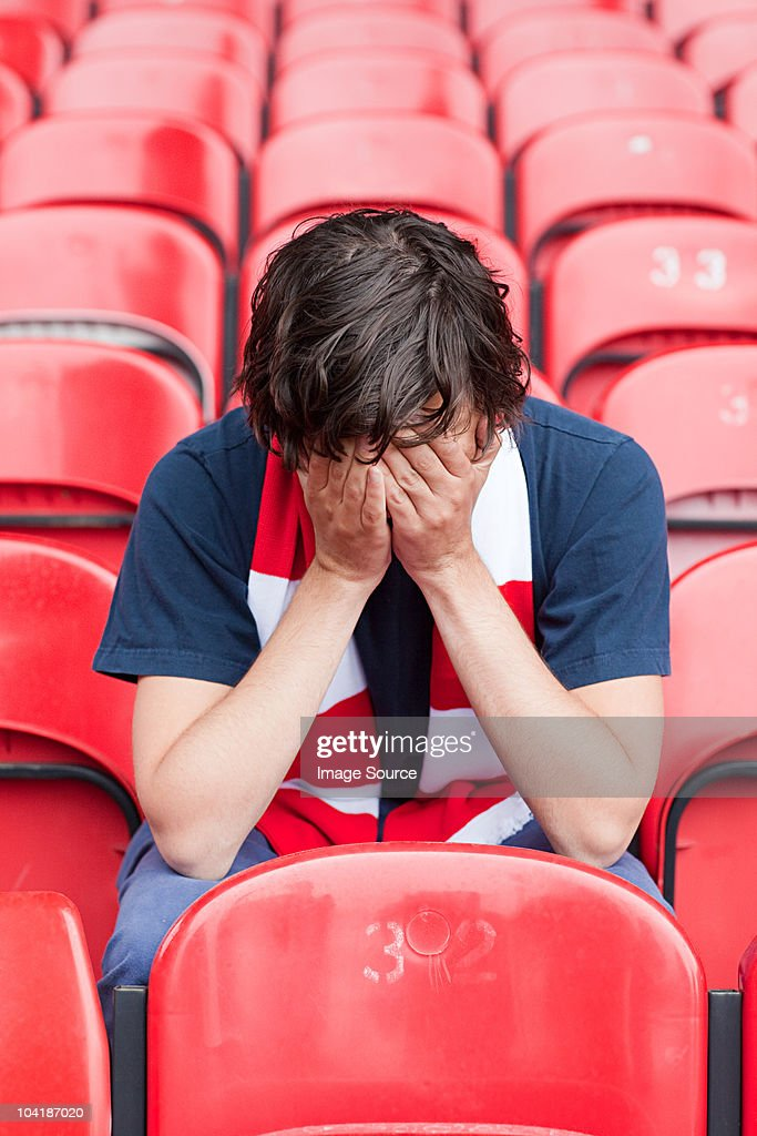 Disappointed football fan in empty stadium : Stock Photo