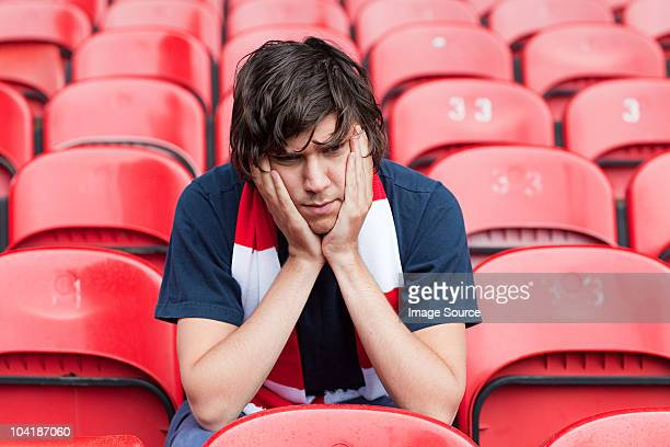 disappointed football fan in empty stadium - nederlaag stockfoto's en -beelden