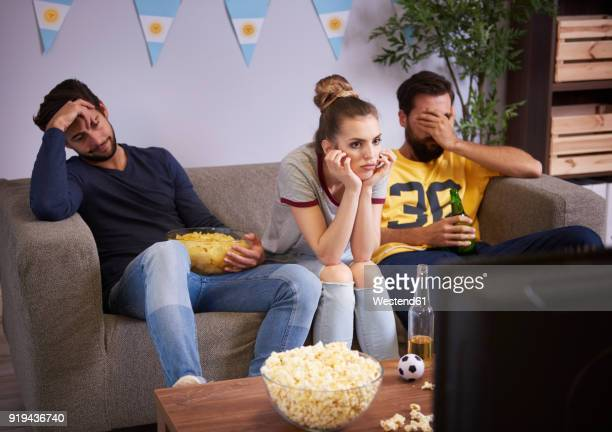 disappointed friends sitting on the sofa watching tv - defeat stock pictures, royalty-free photos & images