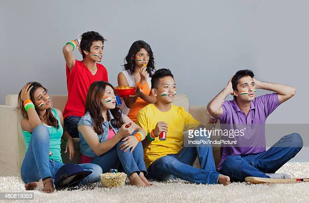 Disappointed friends watching cricket match in living room