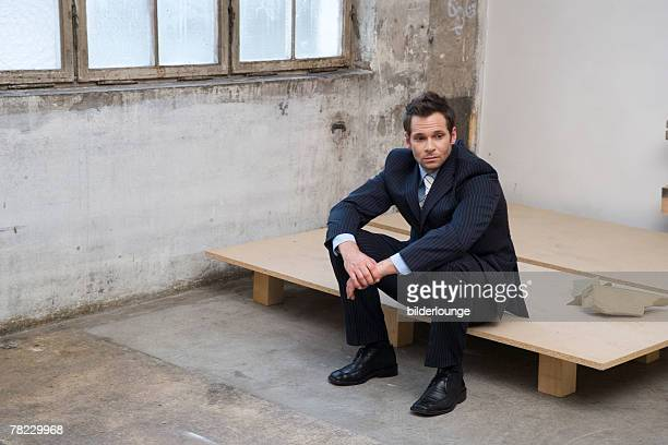 disappointed looking businessman sitting in empty factory building