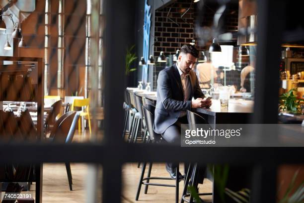 disappointed man looking at smartphone while sitting at bar - one man only stock pictures, royalty-free photos & images