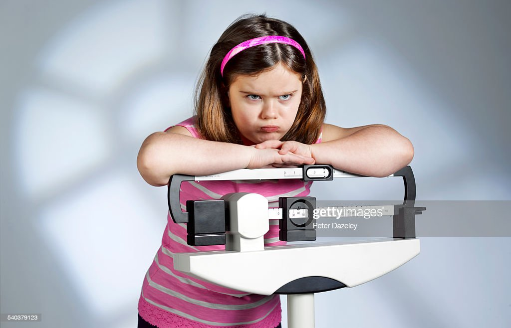 Disappointed overweight girl on scales : 圖庫照片