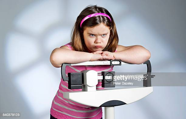 Disappointed overweight girl on scales