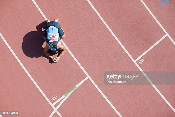 disappointed runner kneeling on track - defeat stock photos and pictures