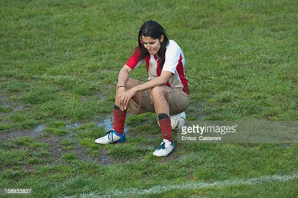 Disappointed soccer player sitting on ball