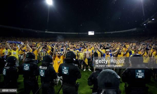 Disappointed supporters of Braunschweig enter the pitch after German Bundesliga relegation second leg football match between Eintracht Braunschweig...