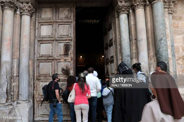 Disappointed visitors and worshippers gather in front of the doors of the Church of the Holy Sepulchre in Jerusalem's Old City on May 24 as they...