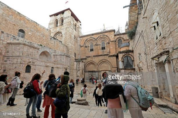 Disappointed visitors and worshippers gather in front of the shut doors of the Church of the Holy Sepulchre in Jerusalem's Old City on May 24 closed...