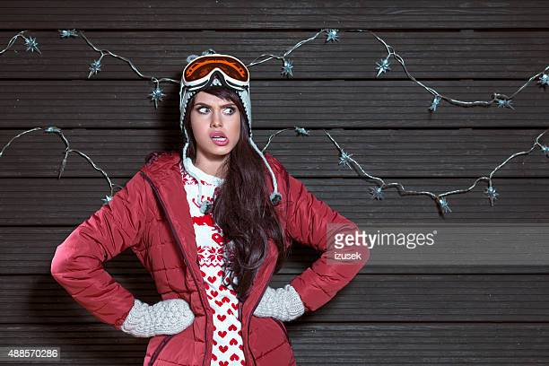 Disappointed woman in winter outfit, wearing puffer jacket and goggle