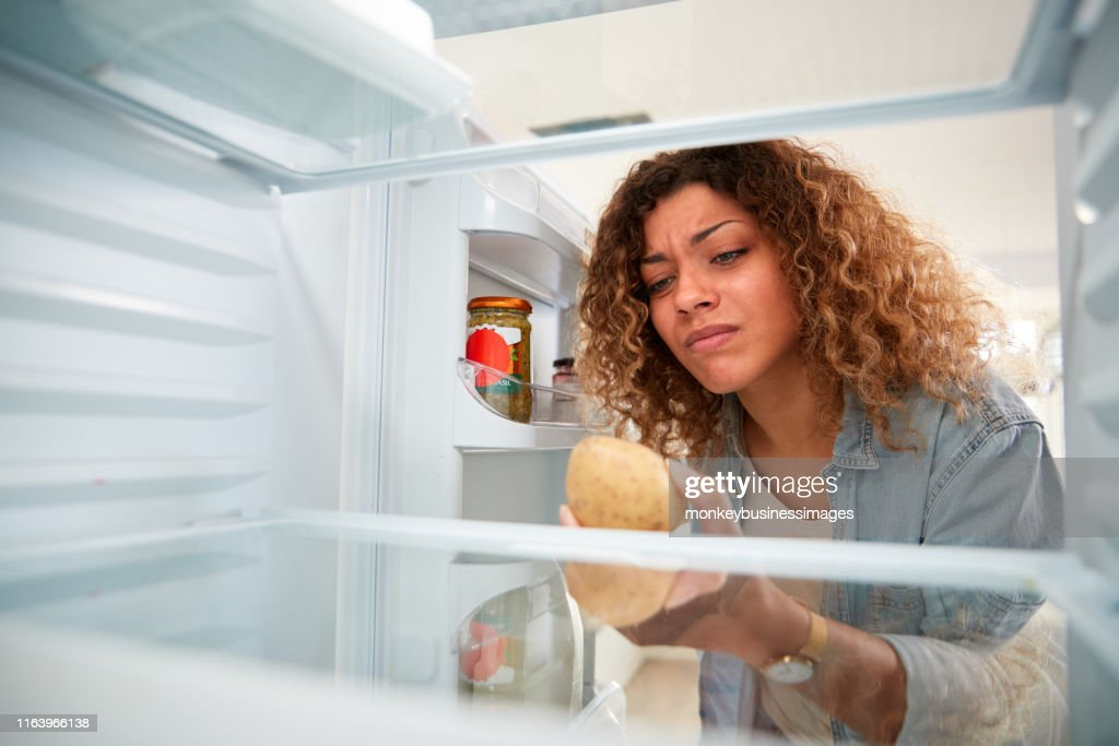 Disappointed Woman Looking Inside Refrigerator Empty Except For Potato On Shelf : Stock Photo