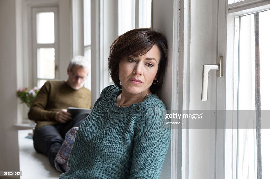 Disappointed woman with man in background : Stock Photo