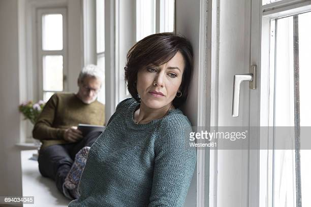 Disappointed woman with man in background