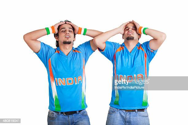 Disappointed young male friends in jerseys standing over white background
