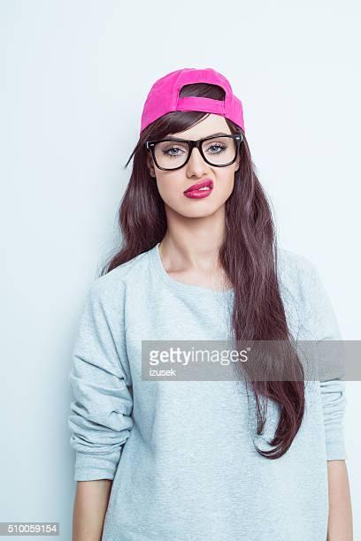 がっかりを着ている若い女性のなかのグラス、ピンクのベースボールキャップ