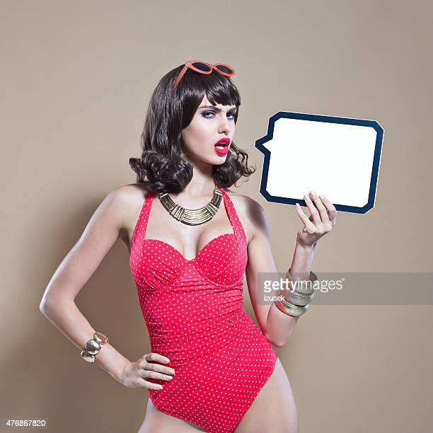 Disappointed young woman wearing red swimsuit holding speech bubble