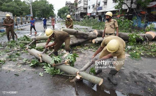 Disaster Management teams clear the streets of uprooted trees at Esplanade after Cyclone Amphan on May 21 2020 in Kolkata India