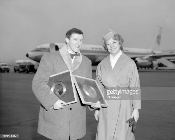 Disc Jockey Jimmy Savile at London Airport with Pan American stewardess Birgit Johansson with two gold disc's one is for American singer Elvis...