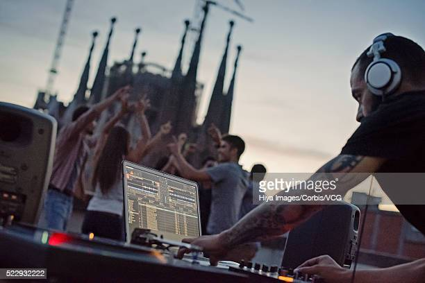 Disc jockey playing on roof terrace with group of people dancing in background