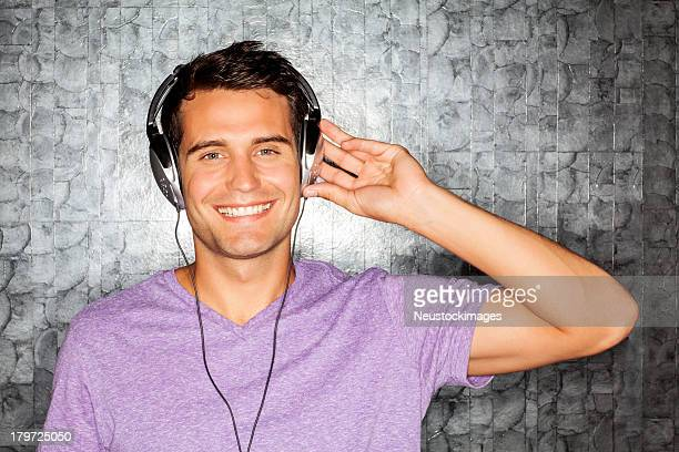 ディスクジョッキー着用のヘッドフォンで音楽を聞くナイトクラブ