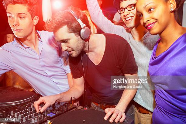 Disc jockey with group of people behind mixing desk