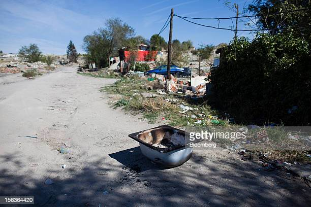 A discarded basin sits on a dirt track near demolished shacks in the Canada Real shanty town near Madrid Spain on Wednesday Oct 17 2012 Spain's...