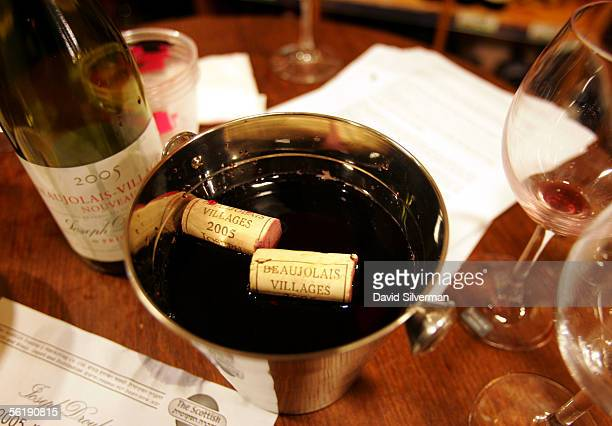 Discarded Beaujolais Nouveau 2005 bottle corks float in a spitoon full of wine during a celebration for the young wine after midnight November 17...