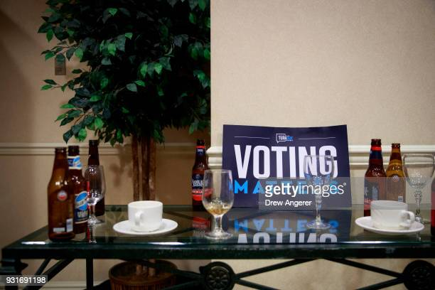 Discarded beer bottles and wine glasses sit on a table during an election night event for Conor Lamb Democratic congressional candidate for...